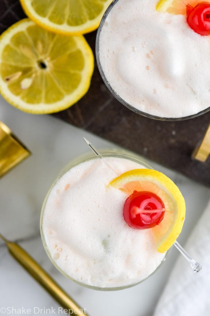 two glasses of vodka sour with frothy egg white, fresh lemon slices, and cherry garnish