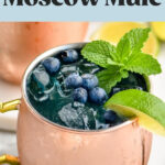 two copper mugs of blue mules with ice, blueberries, lime wedge, and mint leaves