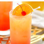 glass of tequila sunrise with ice, orange slice and cherry garnish
