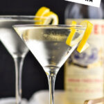 two glasses of Vesper Martini with lemon twist garnish and bottle of Lillet blanc in the background
