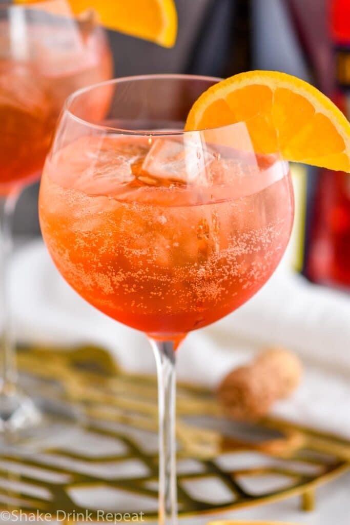 glass of aperol spritz with ice and fresh orange slice