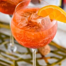 glass of Aperol Spritz with ice, fresh orange slice garnish with bottle of sparkling wine in the background