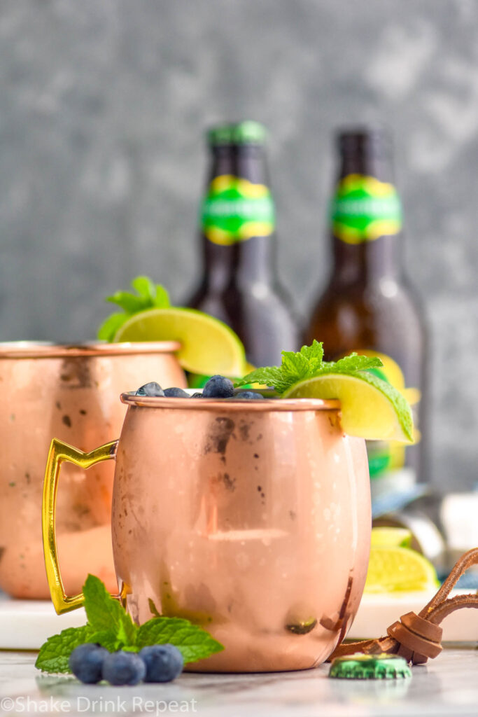 two copper mugs of blue mules with ice, blueberries, lime wedge, and mint leaves and two bottles of ginger beer in the background