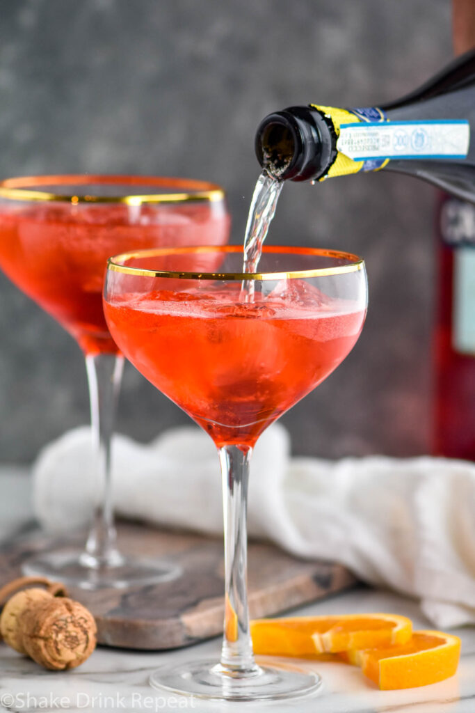 bottle of prosecco pouring into a glass of Campari Spritz with ice and orange slices
