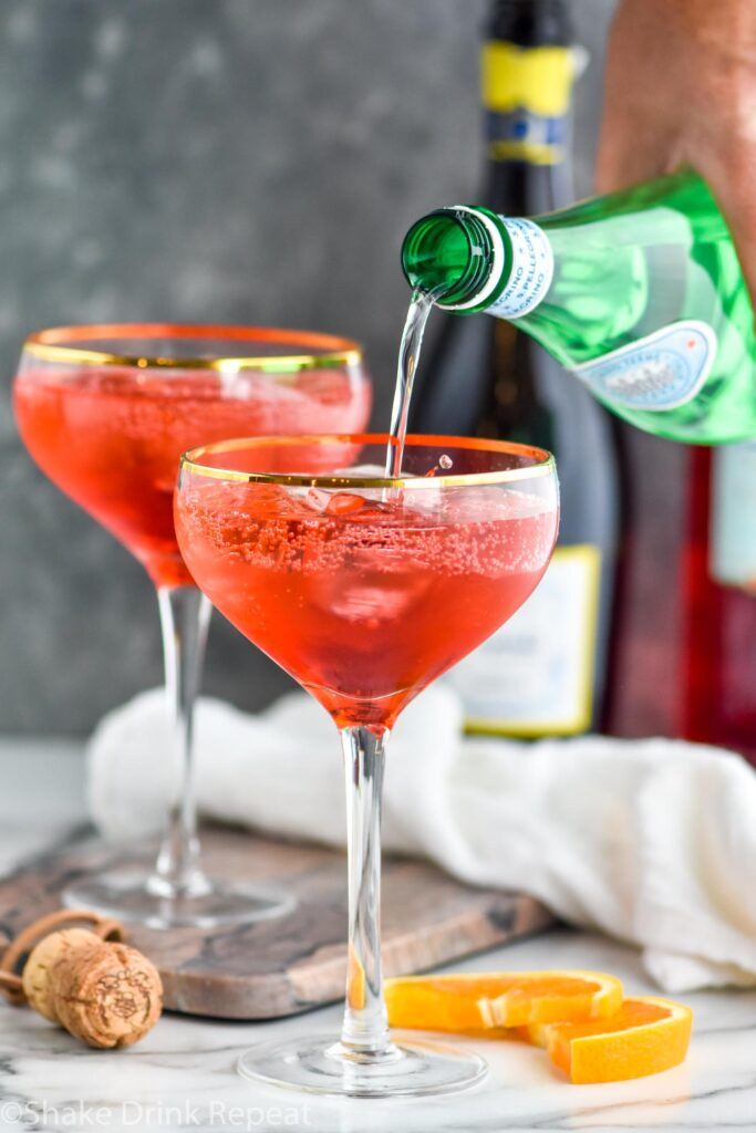 two glasses of Campari Spritz with ice and bottle of club soda being poured into cocktail surrounded by orange slices and bottle of Prosecco