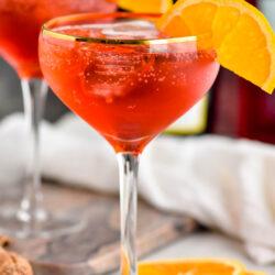 two glasses of Campari Spritz with ice and orange slice garnish