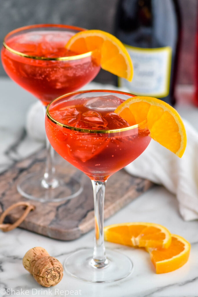 two glasses of Campari Spritz with ice and fresh orange slices surrounded by cork and bottle of sparkling wine