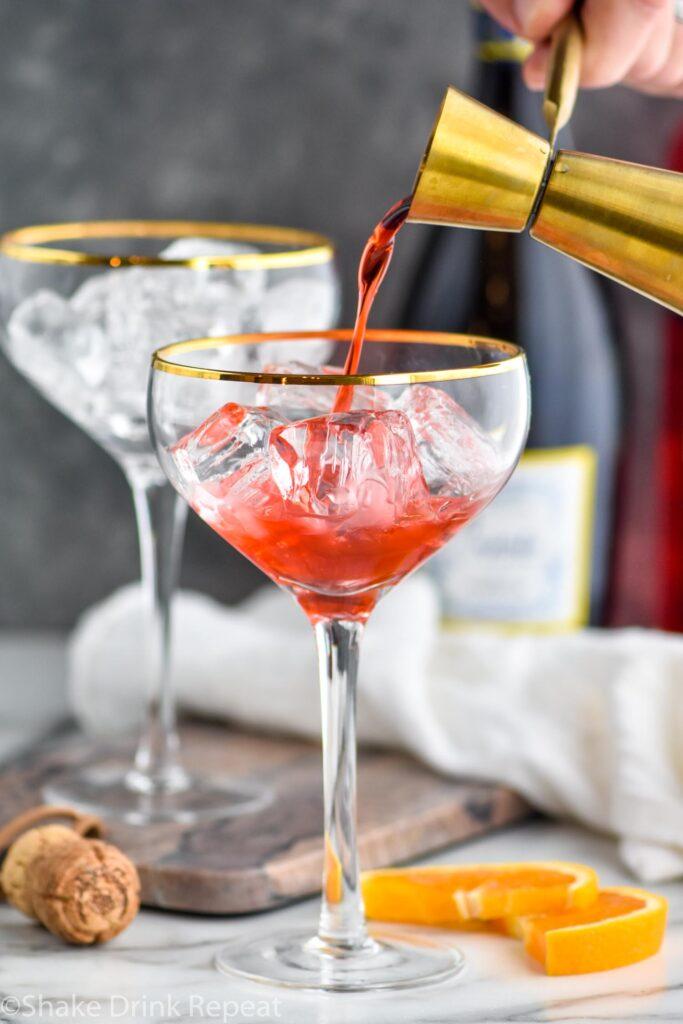 jigger of Campari pouring into a glass of ice to make a Campari Spritz