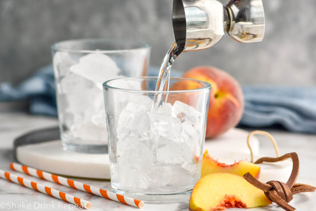 jigger of peach schnapps pouring into a glass of ice to make a Fuzzy Navel cocktail surrounded by fresh peaches and straws