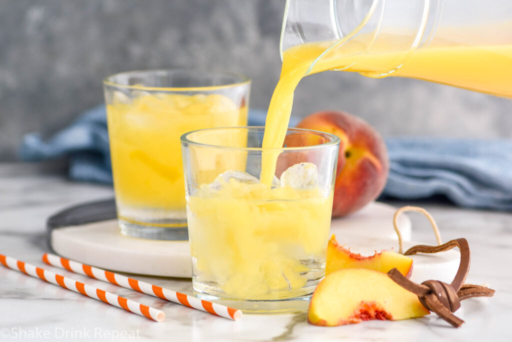 pitcher of orange juice pouring into a glass of Fuzzy Navel recipe with ice surrounded by fresh peach slices and straws