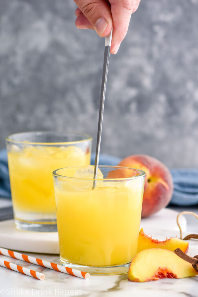 man's hand stirring glass of Fuzzy Navel with ice surrounded by fresh peach slices and straws