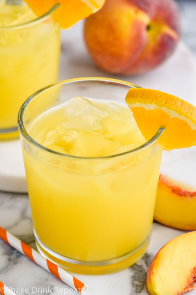 two glasses of Fuzzy Navel cocktail with ice and orange slice garnish surrounded by fresh peach slices and a straw