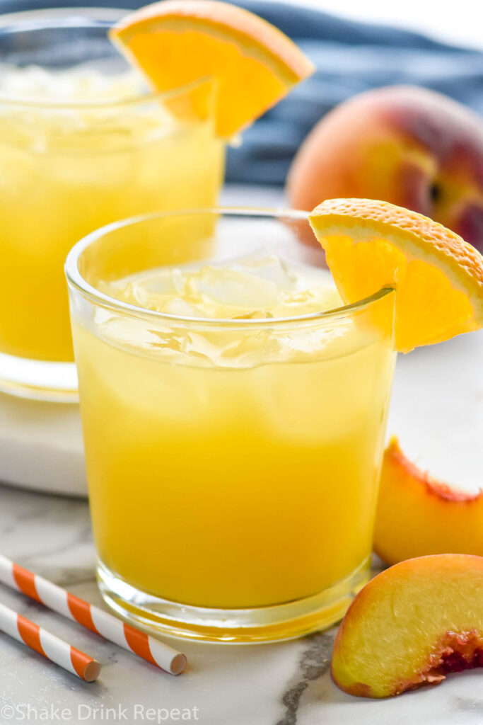 two glasses of Fuzzy Navel with ice and orange slice garnish surrounded by fresh peaches and two straws