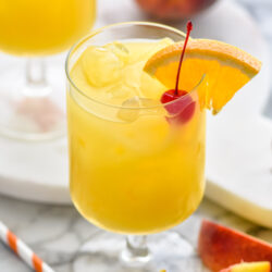 two glasses of Hairy Navel cocktail with ice and garnished with a cherry and slice of orange, surrounded by a straw and fresh peaches