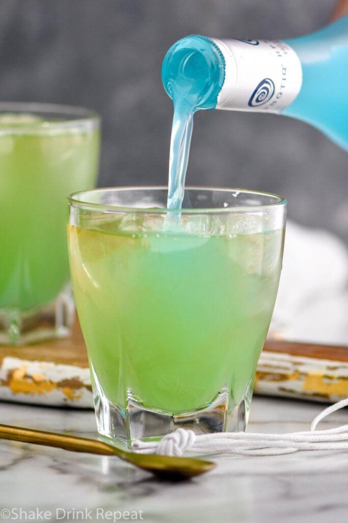 pouring bottle of Hptoniq into a glass of incredible hulk ingredients with ice and gold spoon