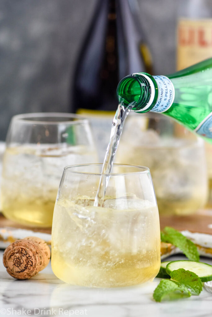 bottle of club soda pouring into a glass of Lillet Spritz with ice, fresh mint leaves, and cucumber slices. Bottle of Prosecco and Lillet Blanc in the background