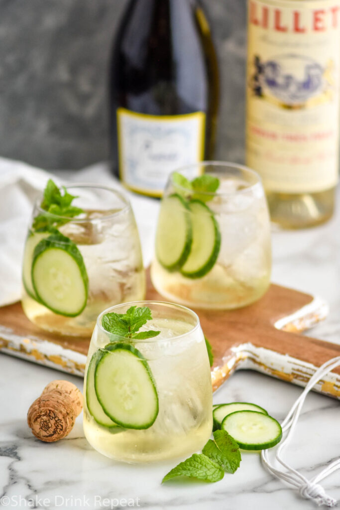 three glasses of Lillet Spritz with ice, fresh mint leaves, and cucumber slices with bottles of Prosecco and Lillet Blanc in the background