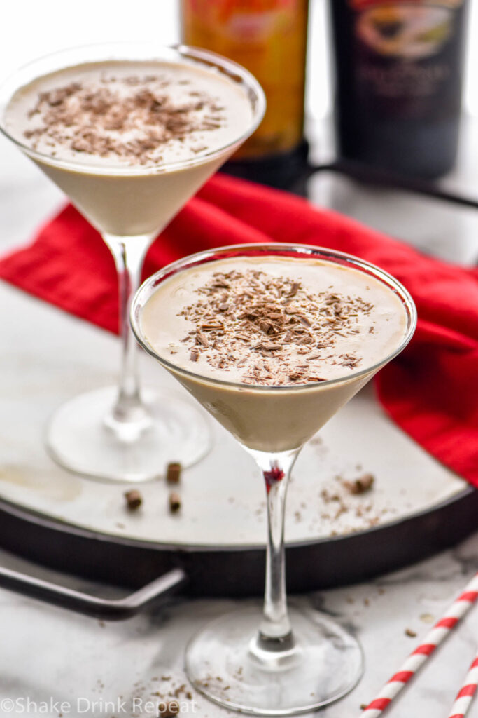 two martini glasses of Mudslide recipe surrounded by chocolate shavings, two straws, a bottle of Bailey's and a bottle of Kahlua