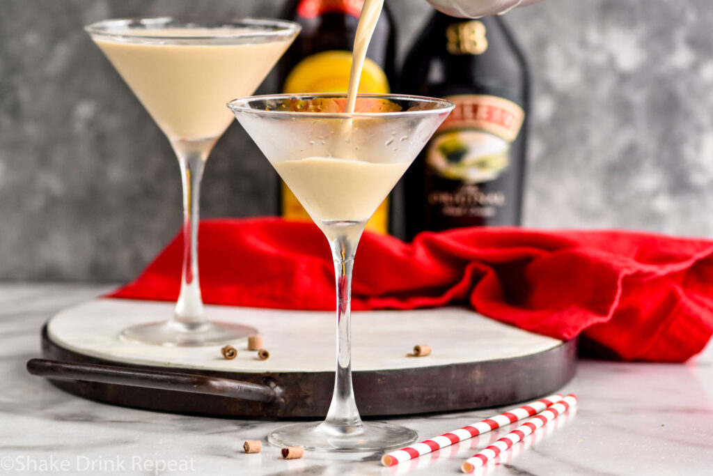 pouring Mudslide recipe into a martini glass surrounded by chocolate shavings, two straws, a bottle of Bailey's, and a bottle of Kahlua