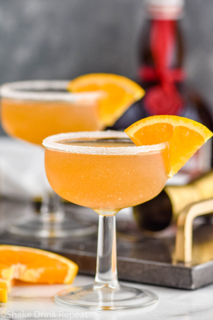 two glasses of Sidecar cocktail with sugared rim, fresh orange slice garnish and bottle of Cognac in the background