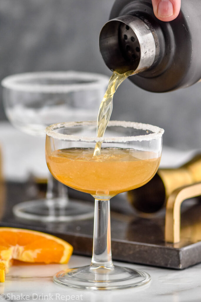 shaker of Sidecar ingredients pouring into a glass with sugared rim surrounded by orange slice