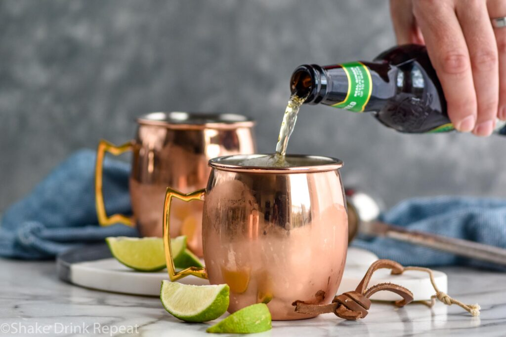 man pouring bottle of ginger beer into a copper mug of Tequila Mule ingredients surrounded by fresh lime wedges