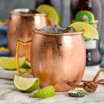 two copper mugs of tequila mules with ice, fresh lime wedges, and bottles of ginger beer