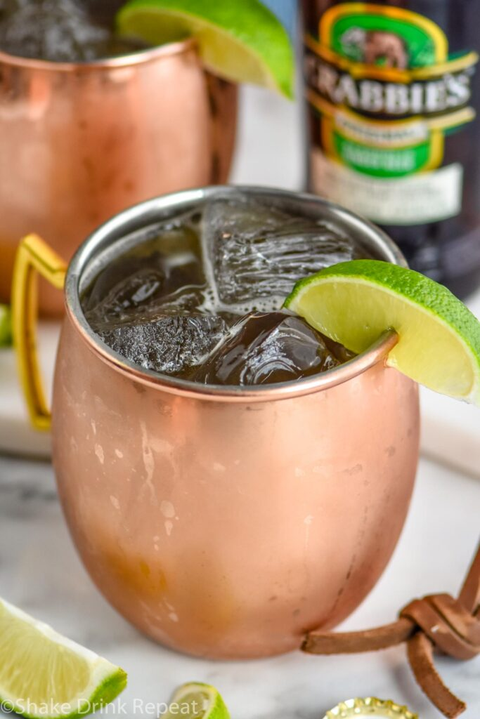 copper mug of Tequila Mule with ice, lime slice, and bottle of ginger beer