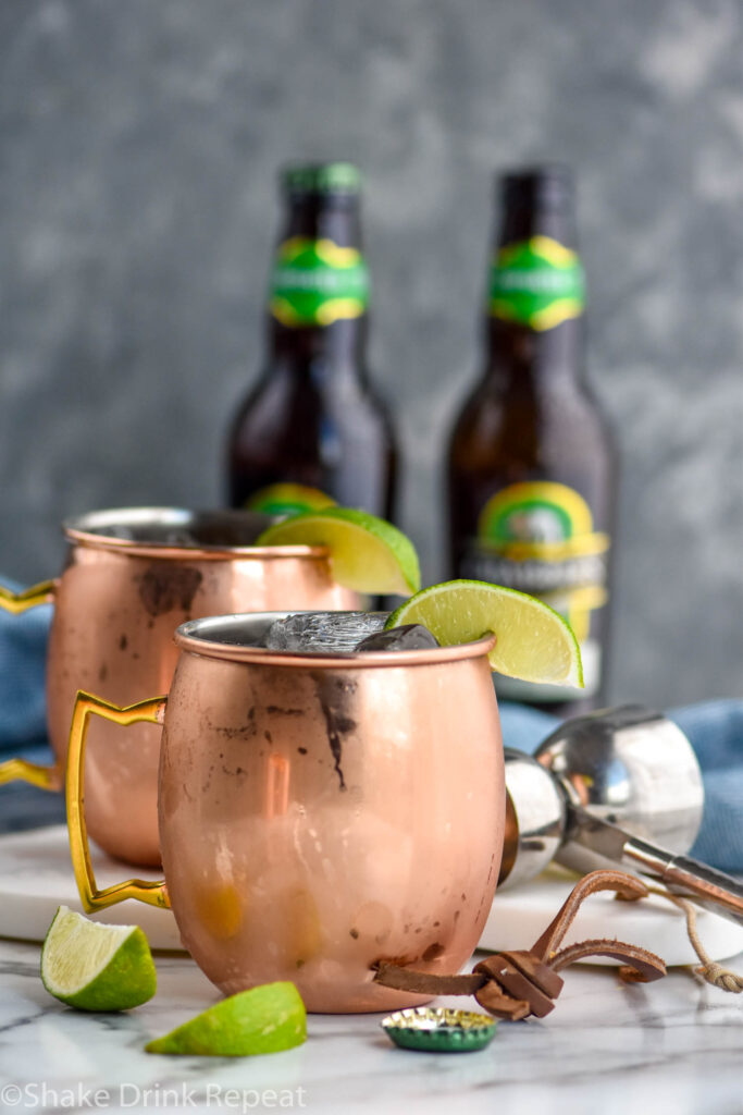 two copper mugs of tequila mules with ice, lime, and two bottles of ginger beer in the background