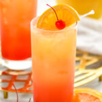 two glasses of tequila sunrise with ice and orange slice and cherry garnish