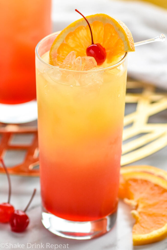 glass of tequila sunrise with ice and an orange slice and cherry garnish