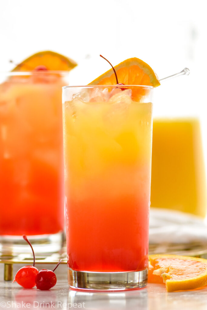 two glasses of tequila sunrise with ice and fresh orange slice and cherry garnish