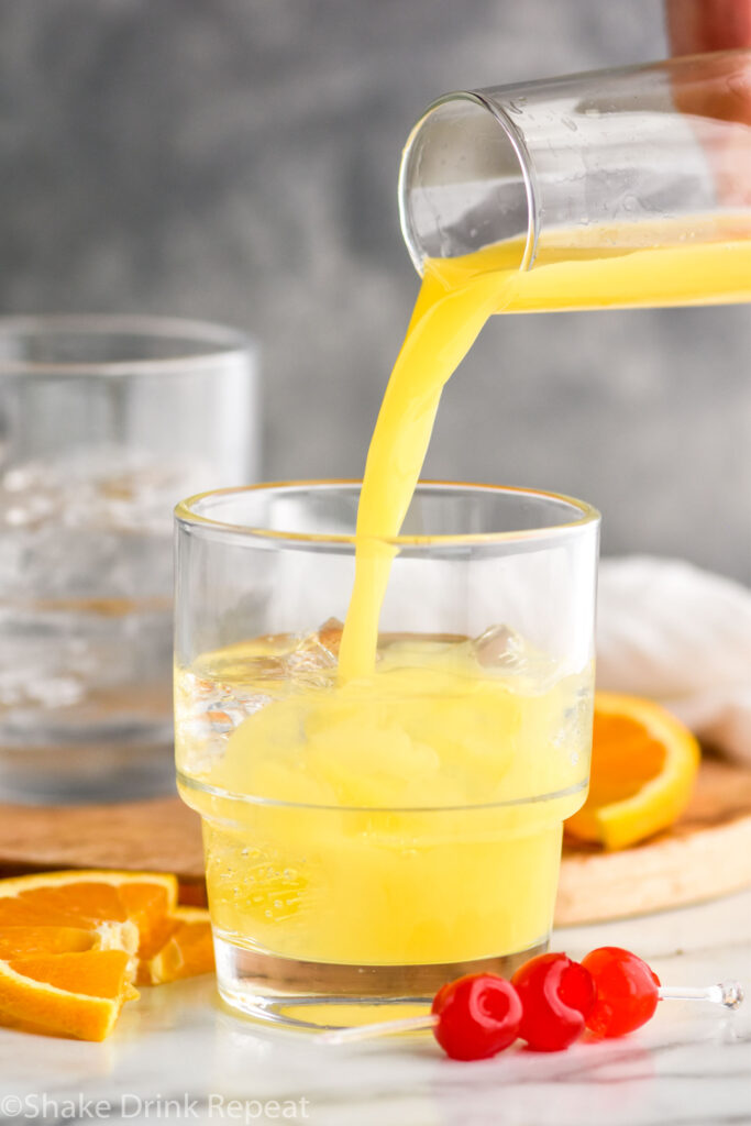 pouring orange juice into a glass of tequila sunset recipe surrounded by cherries and orange slices