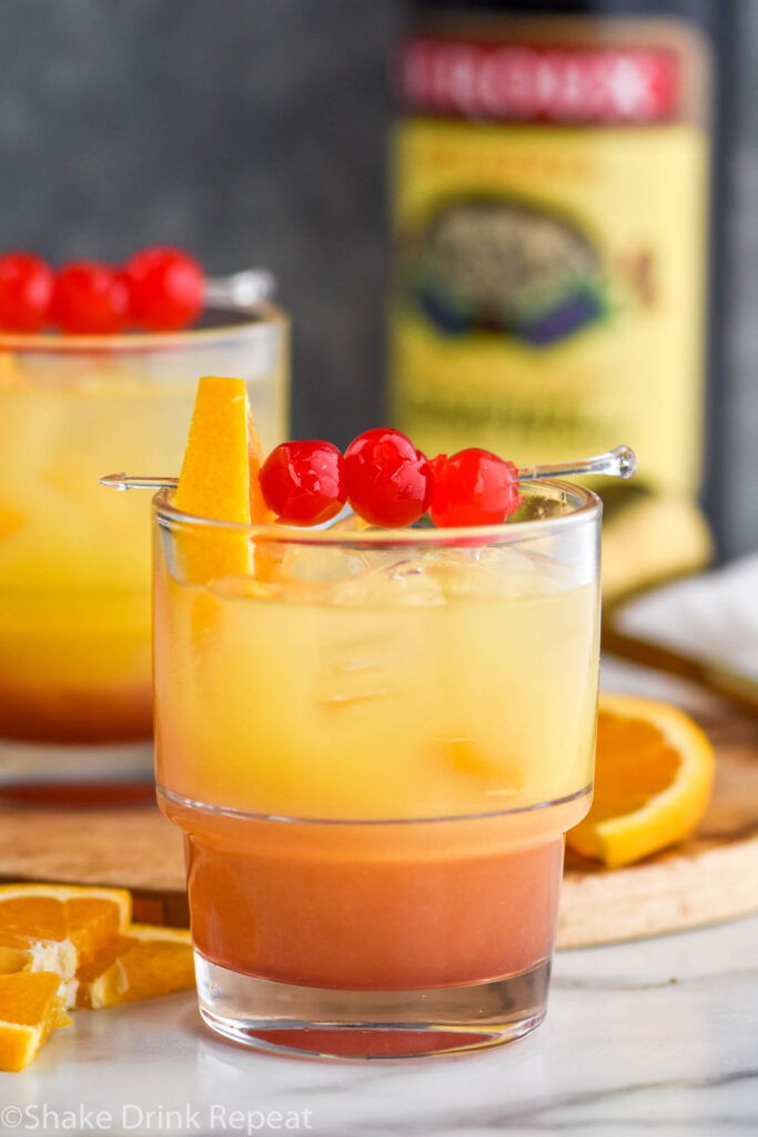 two glasses of tequila sunset with orange and cherry garnish and bottle of blackberry brandy in the background