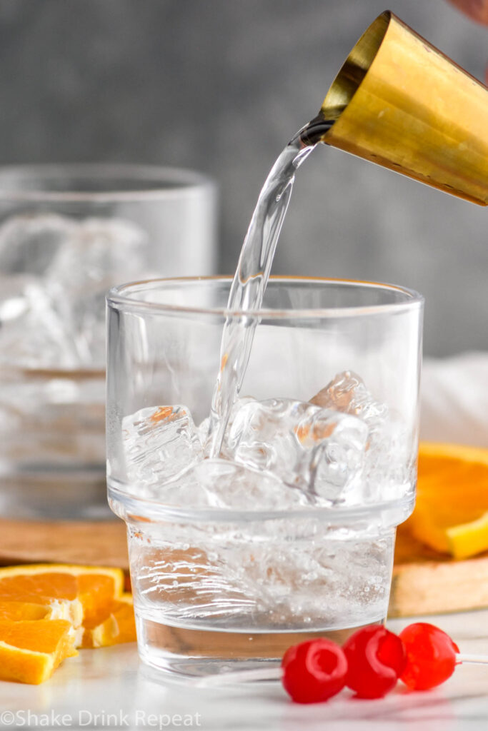 jigger of tequila pouring into a glass of ice to make a tequila sunset recipe surrounded by cherries and orange slices