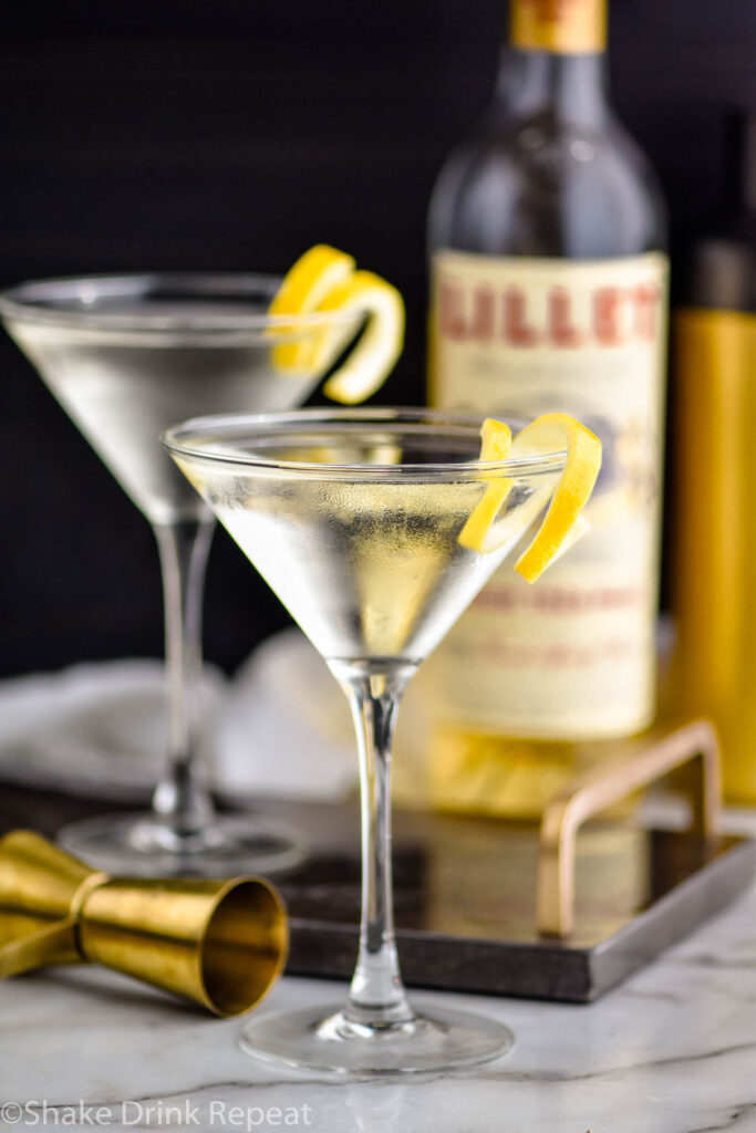 two martini glasses of Vesper Martini with lemon twist garnish surrounded by bottle of Lillet Blanc and jigger
