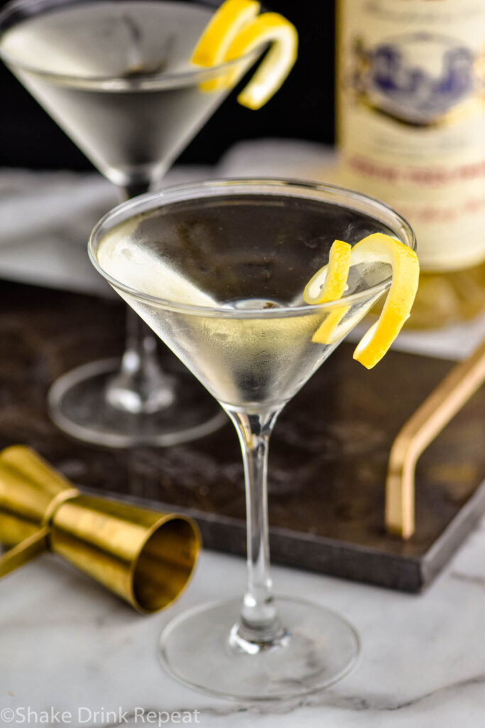 two martini glasses of Vesper Martini with lemon twist garnish surrounded by jigger and bottle of Lillet Blanc