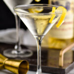 two martini glasses of Vesper Martini with lemon twist garnish and bottle of Lillet Blanc and jigger in the background