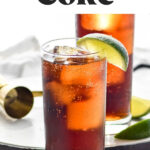 glass of rum and coke with ice and slices of lime