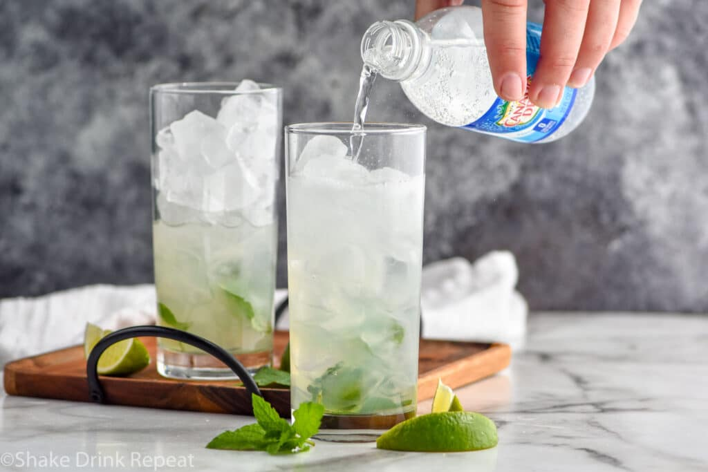 man pouring bottle of club soda into a glass of ice and Mojito ingredients surrounded by fresh mint leaves and lime wedges
