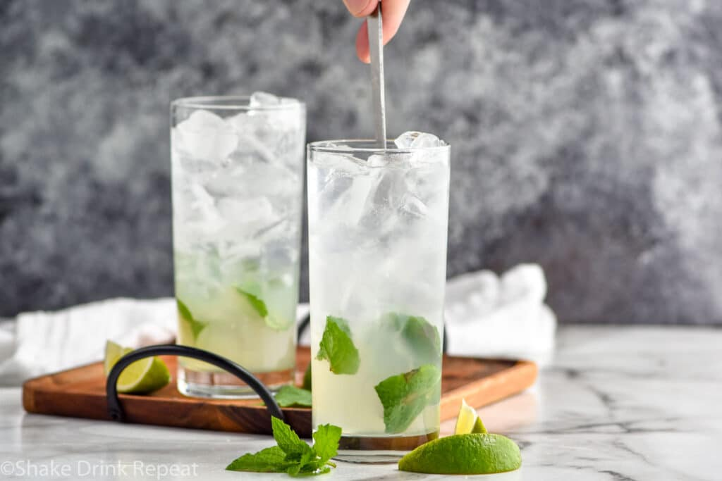 man stirring glass of Mojito recipe ingredients with ice and fresh mint leaves with a spoon