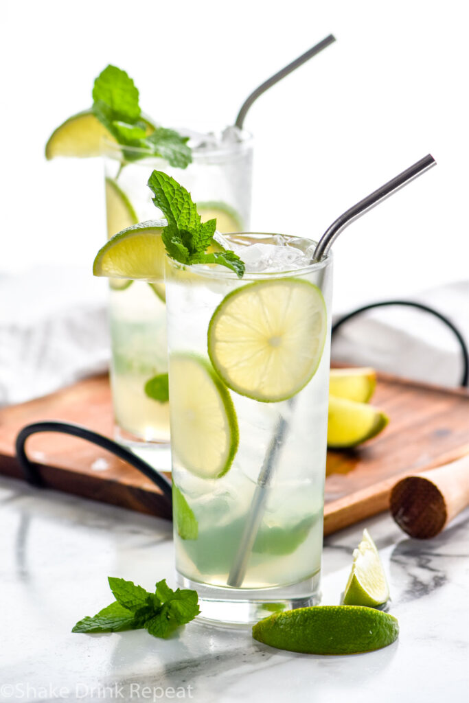 two glasses of Mojito with ice, straws, fresh mint leaves, and lime wedges