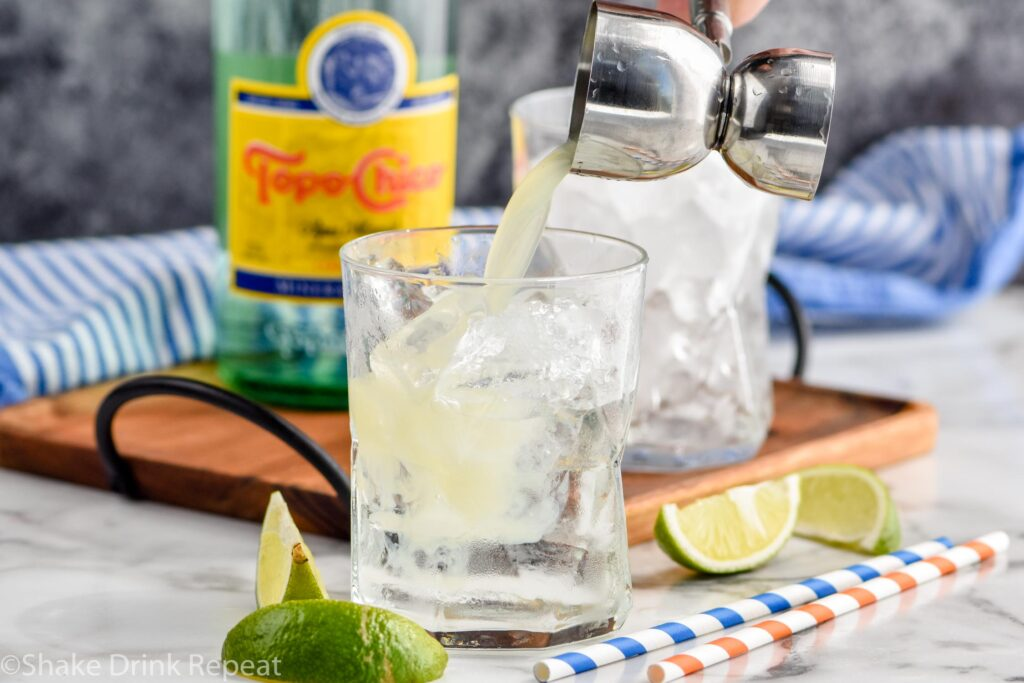 Jigger of lime juice being added to glass of Ranch Water ingredients and ice surrounded by fresh lime wedges, straws, and bottle of Topo Chico
