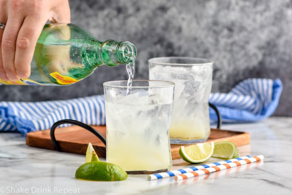 man pouring bottle of Topo Chico into a glass of Ranch Water ingredients and ice surrounded by fresh lime wedges and straws