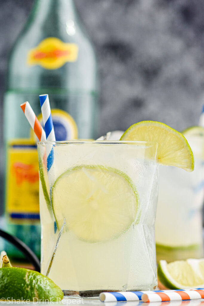 glass of Ranch Water with ice, straws, and fresh lime wedges