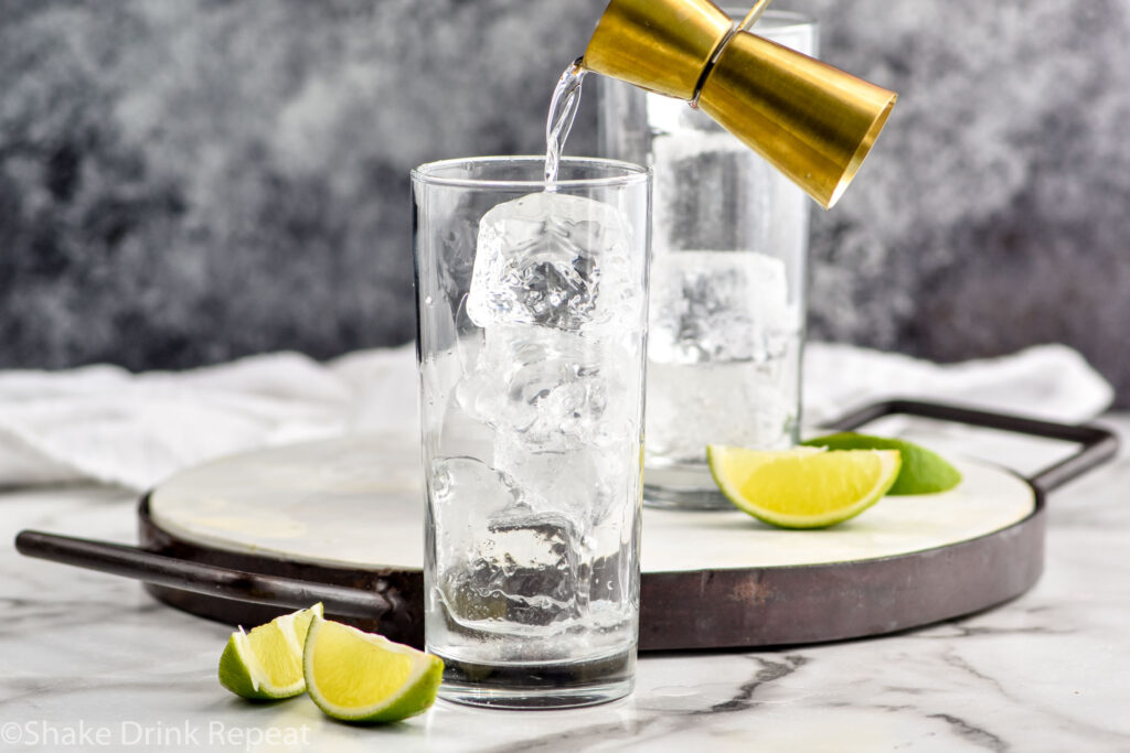 jigger of rum pouring into a glass of ice to make a rum and coke recipe surrounded by slices of lime
