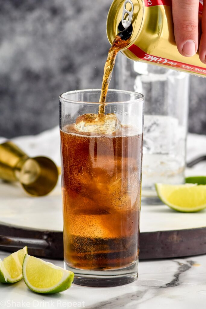 man's hand pouring can of coke into a glass of ice and rum surrounded by slices of lime and gold jigger