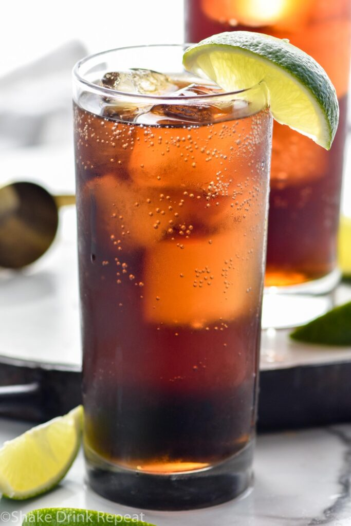 two glasses of rum and coke with ice and slice of lime garnish