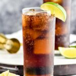 two glasses of Rum and Coke with ice and slices of lime