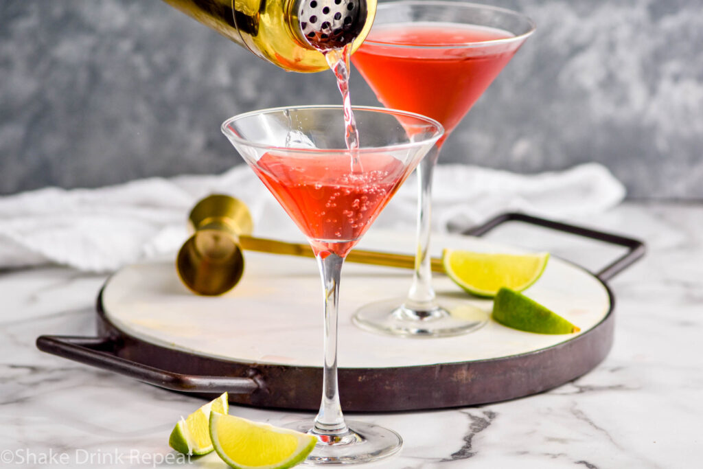 shaker of Woo Woo ingredients pouring into martini glass surrounded by slices of lime and jigger